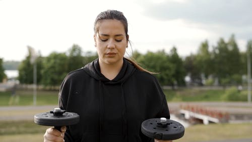 A Woman Training with Dumbbells in a Park