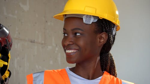 Woman Wearing a Hardhat and Holding a Hand Drill and a Hammer