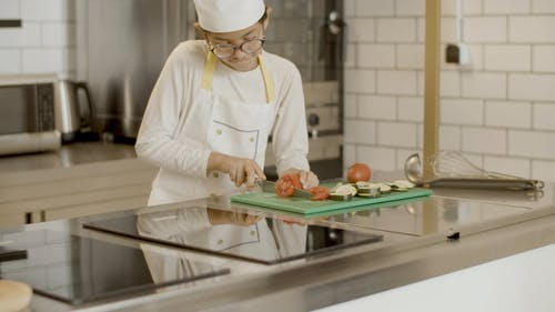 A Girl Slicing Tomato Using a Kitchen Knife