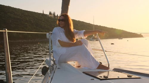 A Woman Holding a Wine Glass While Sitting on a Yacht