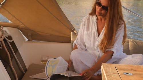 A Woman Reading a Magazine on a Boat