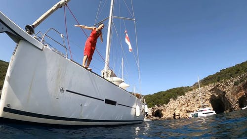 A Woman in a Red Dress Diving from the Side of a Boat