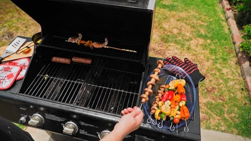 Person Grilling Sausages and Skewers