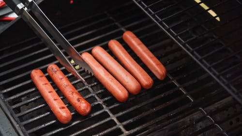 Person Grilling Hot Dogs