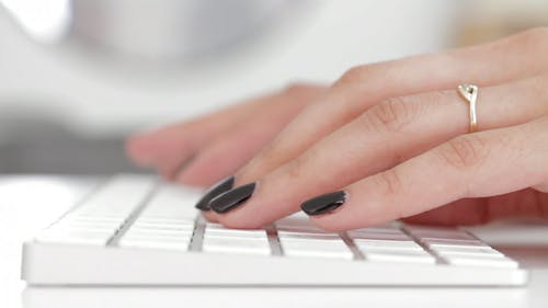 White Keyboard And Black Painted Finger Nails