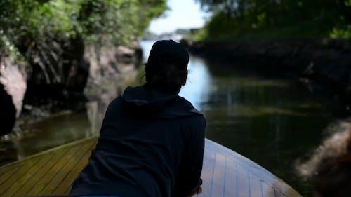 Man Sailing On A Narrow River