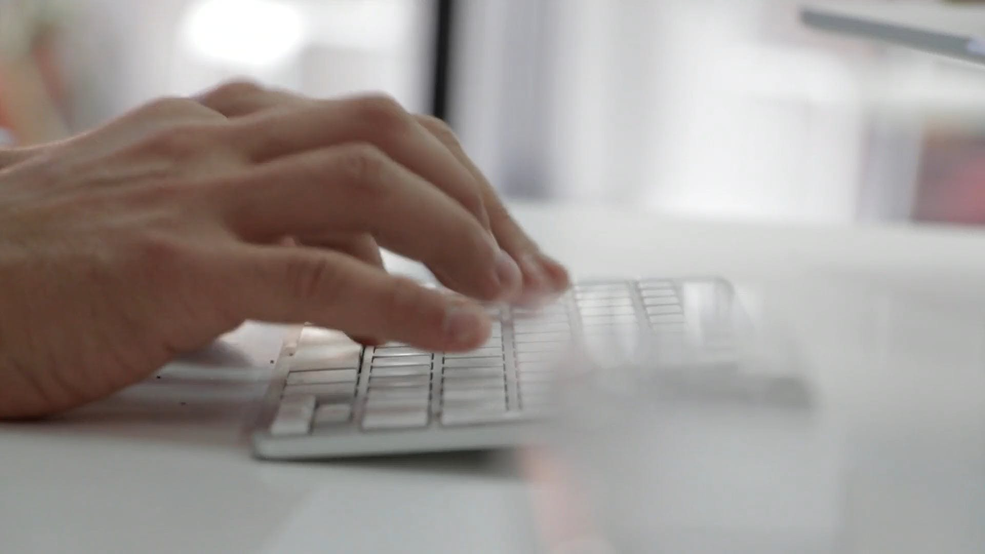 Close Up Video Of Man Typing On A White Keyboard