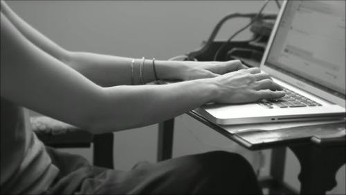 Black And White Video Of A Woman Typing On Keyboard