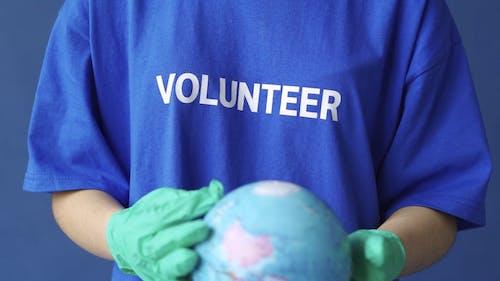 A Volunteer Holding a Globe