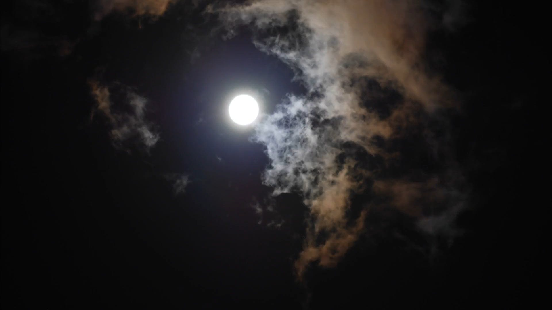 Beautiful Moon Rises through Night Clouds