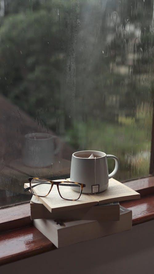 A Cup of Tea on Top of a Stack of Books by a Windowsill