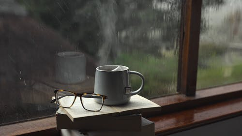A Cup of Tea on Top of a Pile of Books by a Windowsill