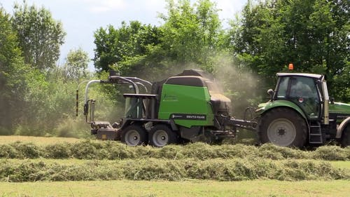 Video Of A Tractor Machine Pulling A Hay Baler