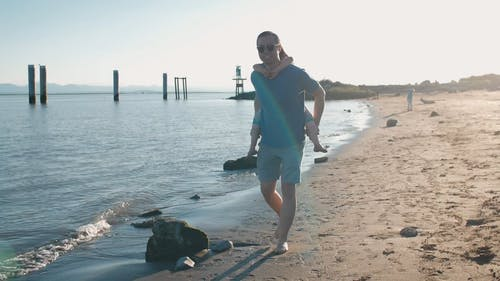 Dad Carrying His Cute Daughter while Walking at the Beach