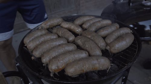Person Grilling Bratwursts
