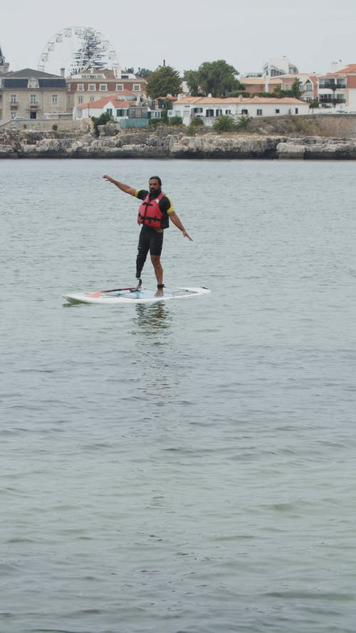 A Man Jumping off a SUP Board