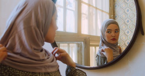 Woman Looking Her Self in Mirror
