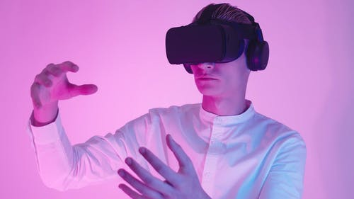 A Man Wearing Virtual Reality Headset while Touching Air