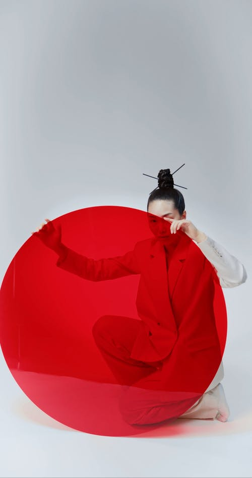 Female Model Posing With a Red Round Cut Out