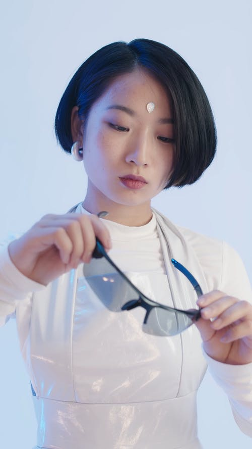A Woman in a Futuristic White Outfit Looking at Sunglasses