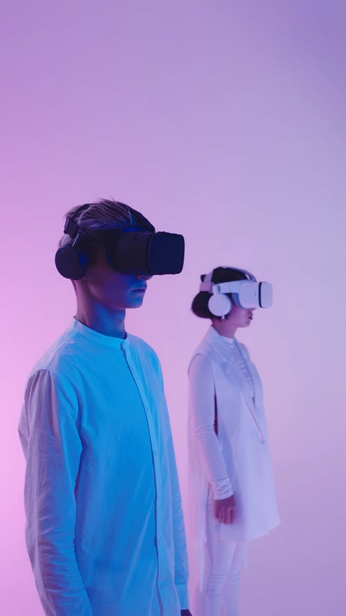 Man and a Woman Looking Around while Wearing VR Headsets