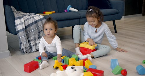 Children Sitting on the Floor while Holding their Toys