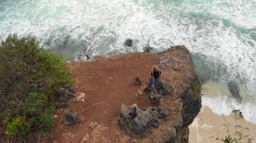 Drone Footage of a Woman Standing Near the Edge of a Cliff