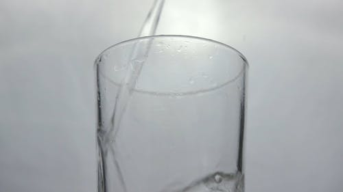 Pouring Water on a Glass Cup