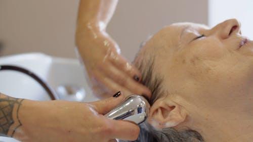 Hairdresser Rinsing Clients Hair