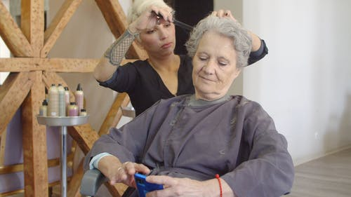 Client Using Her Mobile Phone while Cutting Her Hair