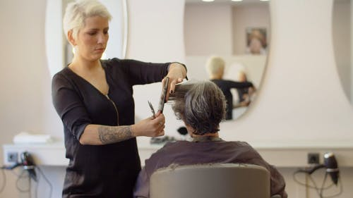Hairdresser Using Scissors while Cutting Clients Hair