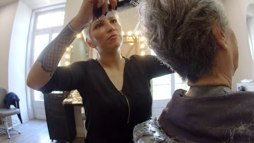 Hairdresser Talking to Her Client while Cutting Her Hair