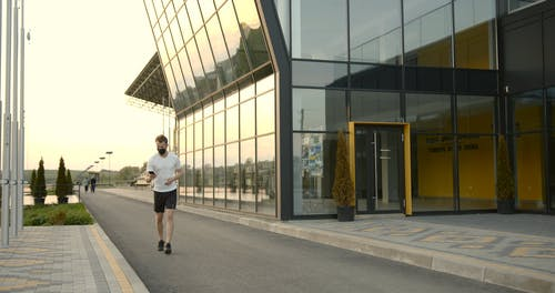 A Man Looking at His Phone While Running
