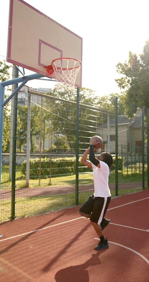 A Man Shooting Near the Basketball Ring