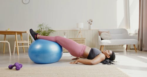 A Woman Training with an Exercise Ball