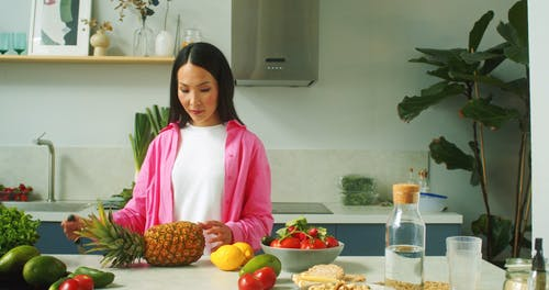A Woman Holding a Knife and Pineapple