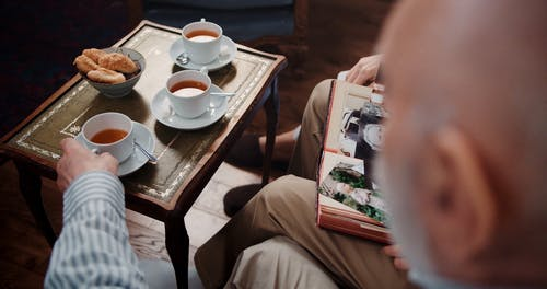 People Looking at Old Photos while Having Tea