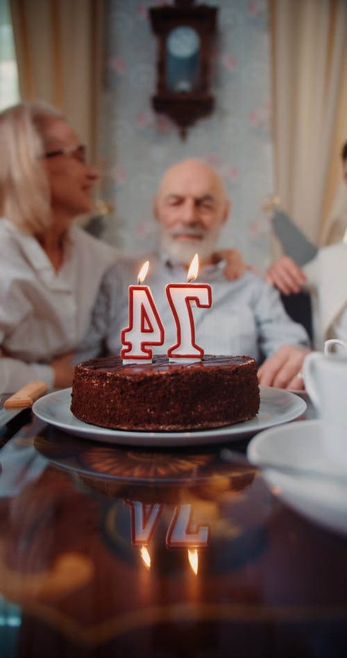An Elderly Man Blowing Candles on a Cake