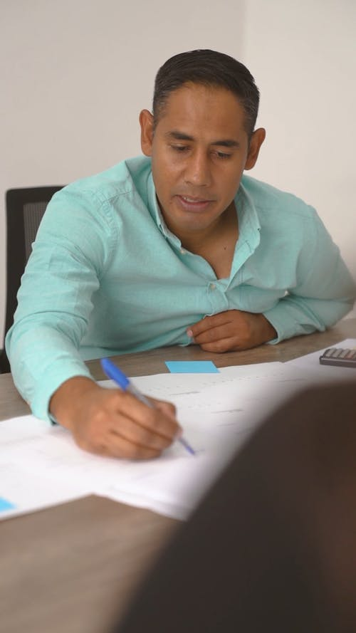 Businessman Discussing While Writing