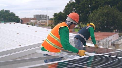 Men In Safety Wear Installing Solar Panels