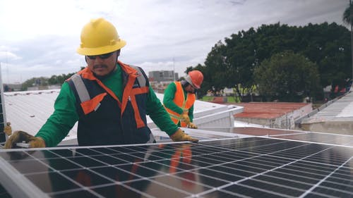 Man Safely Checking The Installation Of Solar Panels