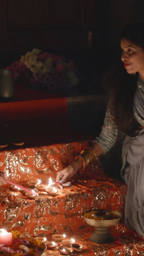 A Woman Lighting Candles