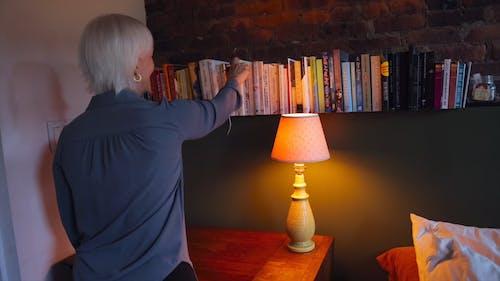 Back View of an Elderly Woman Grabbing a Book from a Bookshelf