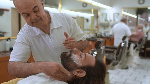 A Barber Putting Powder on a Man's Face