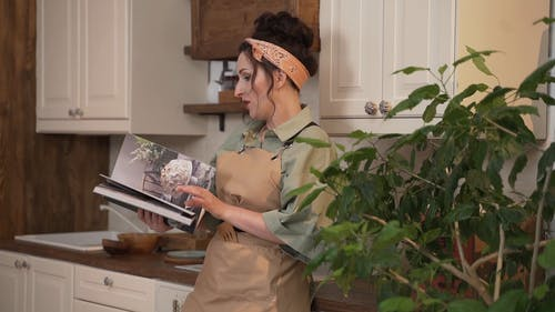 Woman Looking at Magazine In the Kitchen