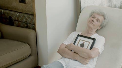 An Elderly Woman Holding a Framed Photograph