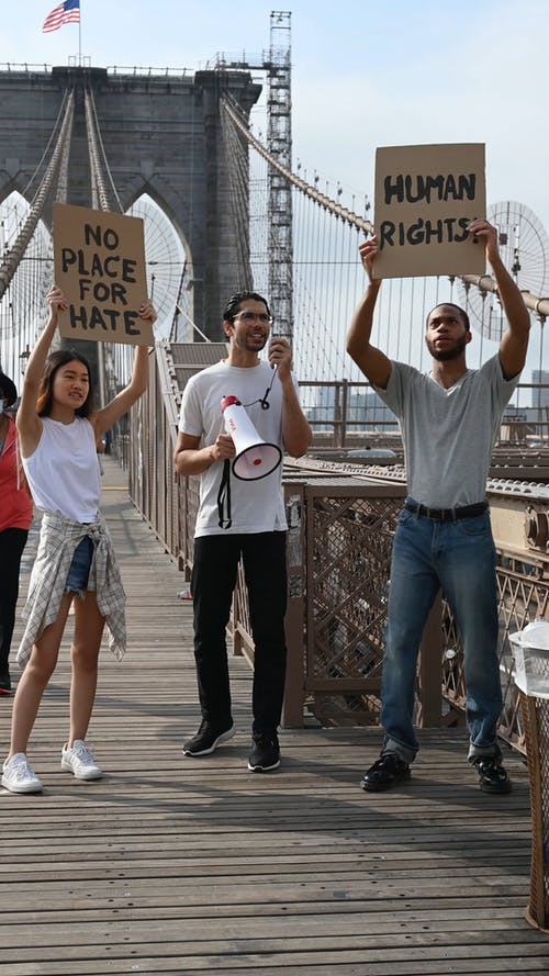 Three People Standing On A Wooden Bridge Making A Protest