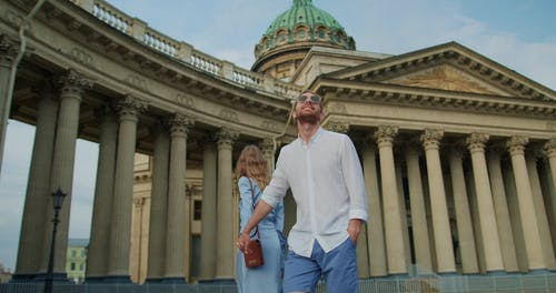 A Couple Holding Hands while Looking at the Tourist Attraction