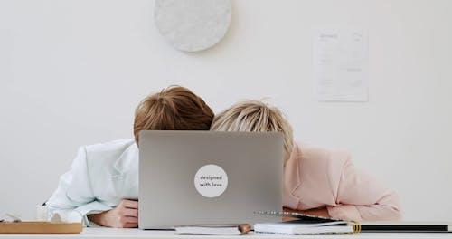 Women Hiding behind a Laptop at an Office