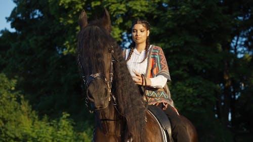 Woman with Braided Hair Riding a Horse